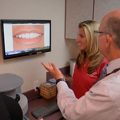 Dentist and patient looking at smile photos