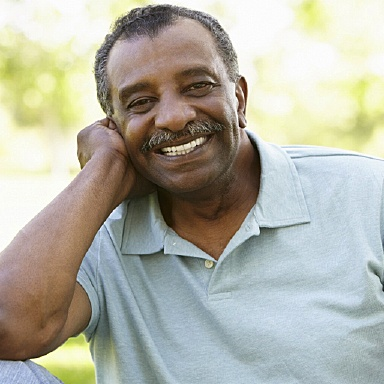Smiling man with All-on-4 dental implant dentures from Long Island implant dentist, Dr. Allan Mohr