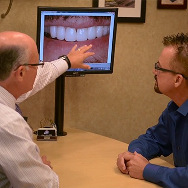 Dentist showing patient smile images