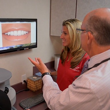 Dentist and patient looking at smile design photos