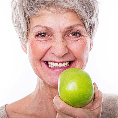 Woman eating an apple with best Long Island implant dentist, Dr. Allan Mohr