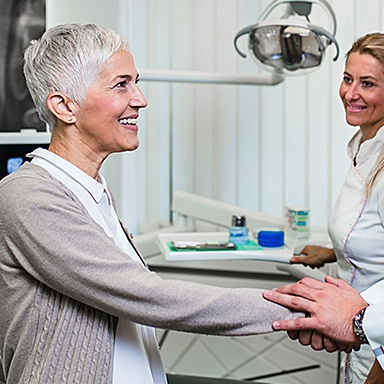 Smiling woman after receiving a dental implant from Dr. Mohr
