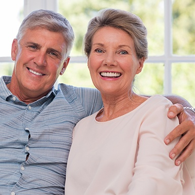 Older couple smiling after receiving the best dental implants on Long Island