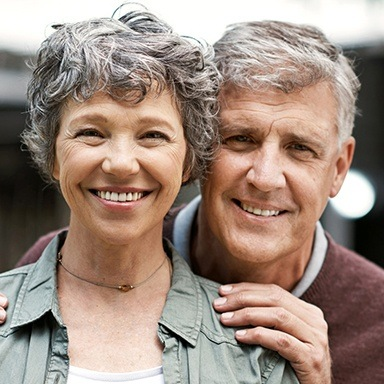 Older Long Island couple smiling with perfect dentures