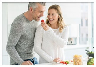 Woman feeding man a strawberry