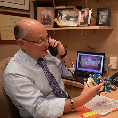 Long Island dental implant dentist, Dr. Allan Mohr, talking with oral surgeon on phone