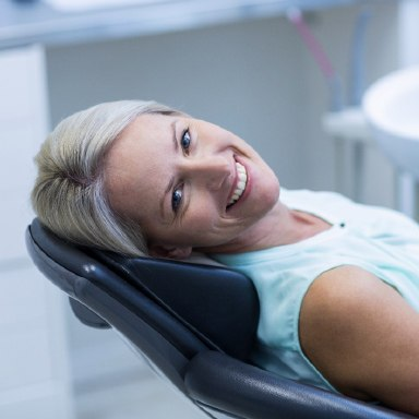 Smiling Long Island dental patient in a dental chair