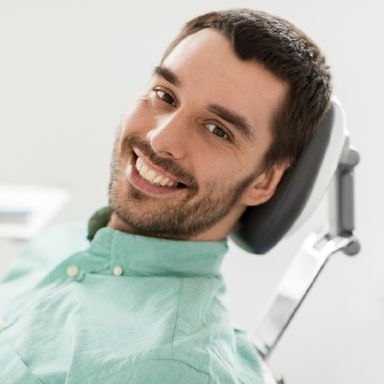 Happy Massapequa Park dental patient in a dental chair