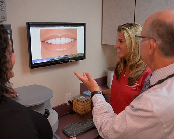 Dentist and patient looking at smile on computer