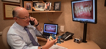 Dentist talking on phone and holding smile model