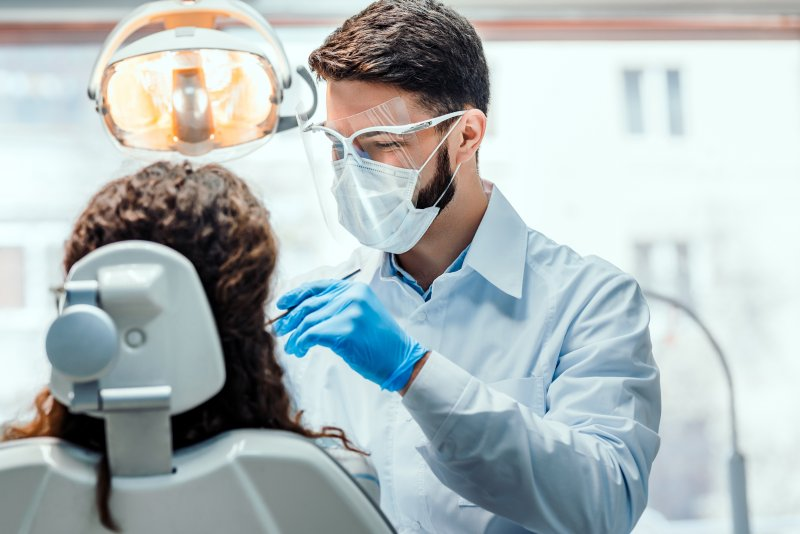a male dentist wearing personal protective equipment while caring for a patient's smile