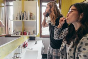 young couple brushing teeth at home