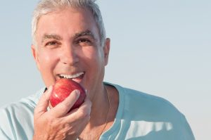 smiling older man eating apple