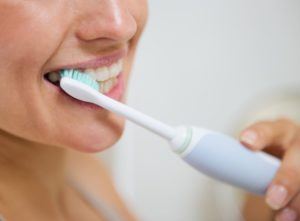 woman brushing with electric toothbrush