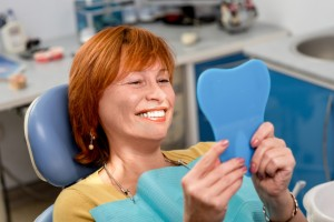 smiling woman with beautiful teeth thanks to the dental implants bellmore residents trust